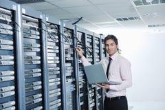 Geschäftsmann mit Laptop im Netzserverraum lizenzfreies stockbild
