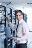 Geschäftsmann mit Laptop im Netzserverraum Stockfotos