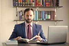 Geschäftsmann mit Laptop und Dokumente am Schreibtisch stockfoto