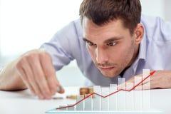 Geschäftsmann mit Münzen im Büro Stockfotografie