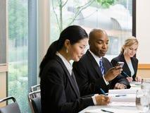 Geschäftsmann mit Mitarbeiter-Versenden von SMS-Nachrichten auf Zelle Stockbilder
