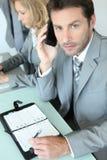 Geschäftsmann mit Mobiltelefon und Anmerkungsauflage Stockfotos