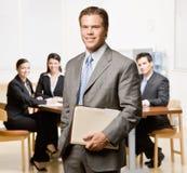 Geschäftsmann mit Notizbuch und Mitarbeitern Stockfotografie