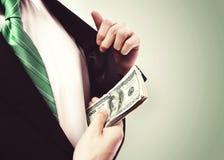 Geschäftsmann mit Pack von Cash in seine Jacken-Tasche Stockbild