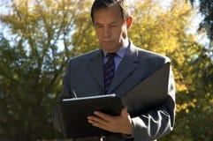 Geschäftsmann mit Papieren draußen Stockbild
