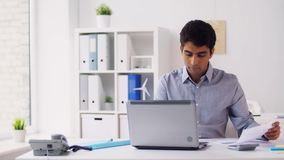 Geschäftsmann mit Papieren schreibend auf Laptop im Büro stock footage
