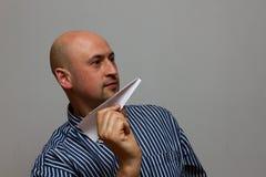 Geschäftsmann mit Papierflugzeug Spielerischer junger Mann im Papierflugzeug haltenen und bei der Stellung lächelnden formalwear lizenzfreie stockbilder