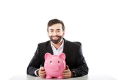 Geschäftsmann mit piggybank durch einen Schreibtisch Stockfoto