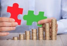 Geschäftsmann mit Puzzlespielstücken und Staplungsmünzen am Schreibtisch Lizenzfreies Stockbild