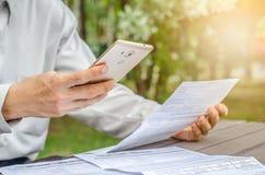 Geschäftsmann mit Rechnungen und intelligentes Telefon am Tisch Lizenzfreie Stockfotografie