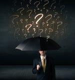 Geschäftsmann mit Regenschirm und vielen gezogenen Fragezeichen Stockfotos