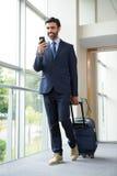 Geschäftsmann mit Rollkoffer unter Verwendung des Handys Stockbild