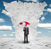 Geschäftsmann mit rotem Regenschirm unter Dokumenten Stockfotos