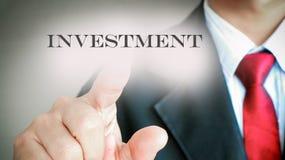 Geschäftsmann mit roter Bindungsvertretungspresse auf Text INVESTITION Stockfotografie