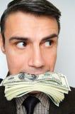Geschäftsmann mit Satz Dollar in einem Mund Stockfotos