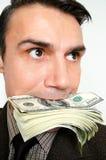 Geschäftsmann mit Satz Dollar in einem Mund Stockfoto