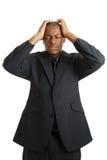 Geschäftsmann mit seinen Händen auf dem Kopf wegen der Störung Lizenzfreie Stockbilder