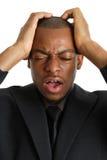 Geschäftsmann mit seinen Händen auf dem Kopf wegen der Störung lizenzfreies stockbild