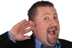 Geschäftsmann mit seiner Hand zu seinem Ohr Stockbild