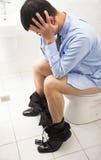 Geschäftsmann mit sitzendem Toilettensitz des frustrierten Ausdrucks Lizenzfreies Stockbild