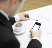 Geschäftsmann mit Smartphonelesenachrichten Stockbild