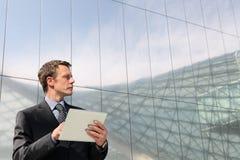 Geschäftsmann mit Tablette, die weit den Himmel untersucht Stockfotografie