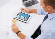 Geschäftsmann mit Tabletten-PC und -kaffee im Büro Lizenzfreie Stockfotos