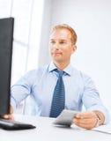 Geschäftsmann mit Taschenrechner, Computer und Papieren lizenzfreies stockfoto