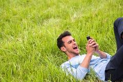 Geschäftsmann mit Telefon auf dem grünen Gras stockfotografie