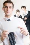 Geschäftsmann mit unbelegter Anmerkungkarte und zwei Geschäftsfrauen Stockfotos