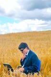 Geschäftsmann mitten in Feld Stockbild