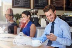 Geschäftsmann With Mobile Phone und Zeitung in der Kaffeestube