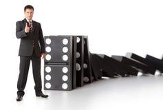 Geschäftsmann nahe einem Stapel Dominos Lizenzfreies Stockfoto