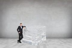 Geschäftsmann nahe großem Eiswürfel Stockbild
