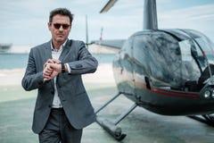 Geschäftsmann nahe privatem Hubschrauber lizenzfreie stockfotografie