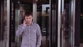 Geschäftsmann nimmt vom Geschäftszentrum heraus und spricht telefonisch stock footage