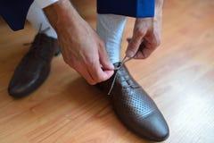 Geschäftsmann- oder Bräutigambindung eine Spitze auf seinen braunen Schuhen Flache Schärfentiefe Stockbilder