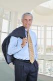 Geschäftsmann in Ofice mit Jacke über Schulter lizenzfreie stockfotos