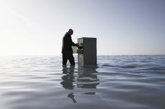 Geschäftsmann Opening Filing Cabinet im Meer Stockfotos