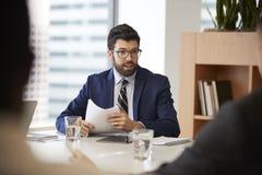 Geschäftsmann With Paperwork Sitting bei Tisch, das Kollegen im modernen Büro trifft lizenzfreies stockfoto