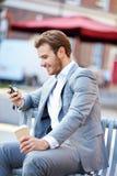 Geschäftsmann On Park Bench mit Kaffee unter Verwendung des Handys Stockfoto