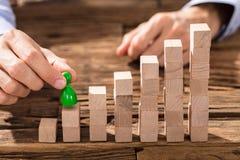 Geschäftsmann-Placing The Green-Zahl auf Block-Stapel Lizenzfreies Stockbild