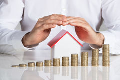Geschäftsmann Protecting House Model mit Staplungsmünzen am Schreibtisch Lizenzfreie Stockfotos