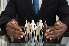 Geschäftsmann-Protecting Paper Cutout-Leute Lizenzfreie Stockfotos
