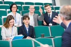 Geschäftsmann-Raising Hand While-Kollege, der Darstellung gibt stockfotografie