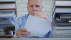 Geschäftsmann Reading Contracts und Dokumente im Büro stockfotos