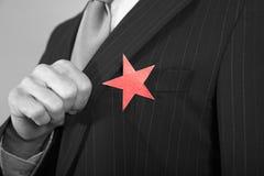 Geschäftsmann With Red Star auf Klage stockfotos
