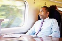 Geschäftsmann Relaxing On Train, das Musik hört Stockbild