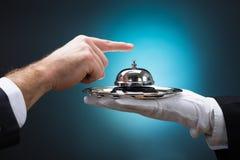 Geschäftsmann Ringing In Service Bell gehalten vom Hotelpagen Stockfotografie