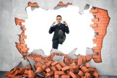 Geschäftsmann ruiniert Backsteinmauer mit seinem Bein auf dem weißen Hintergrund Stockfotografie